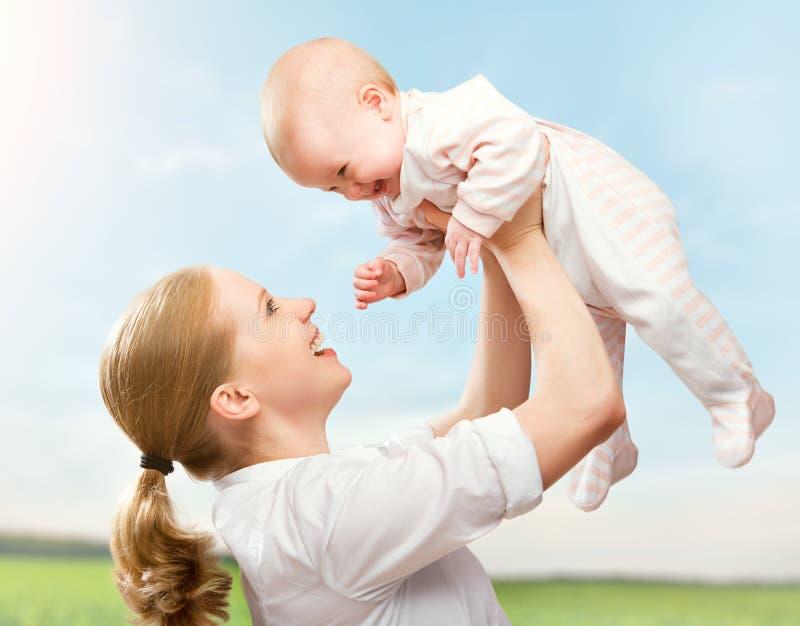 Ευτυχής οικογένεια. Η μητέρα ρίχνει επάνω στο μωρό στον ουρανό στοκ φωτογραφίες