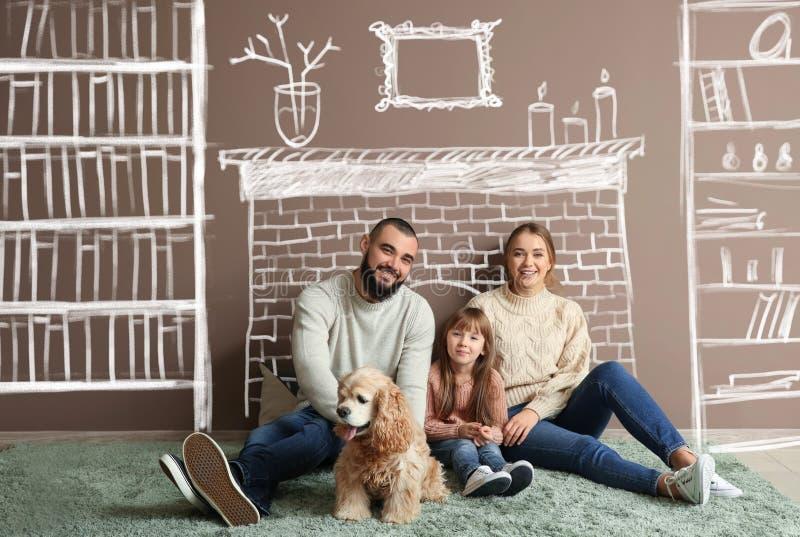 Ευτυχής οικογένεια και χαριτωμένο σκυλί στον τάπητα κοντά στον τοίχο χρώματος στοκ εικόνες