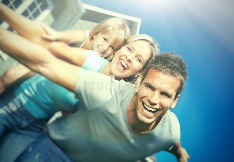 Ευτυχής οικογένεια κοντά στο σπίτι στοκ φωτογραφίες