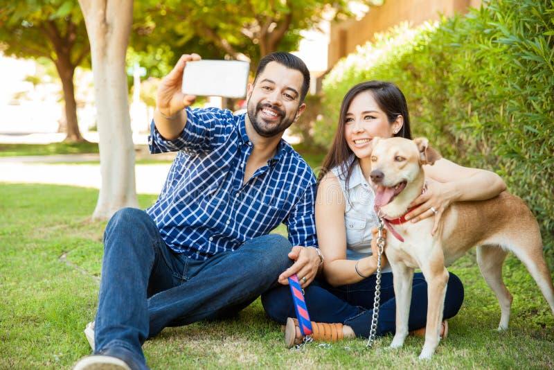 Ευτυχής οικογένεια με ένα σκυλί που παίρνει selfie στοκ φωτογραφία με δικαίωμα ελεύθερης χρήσης