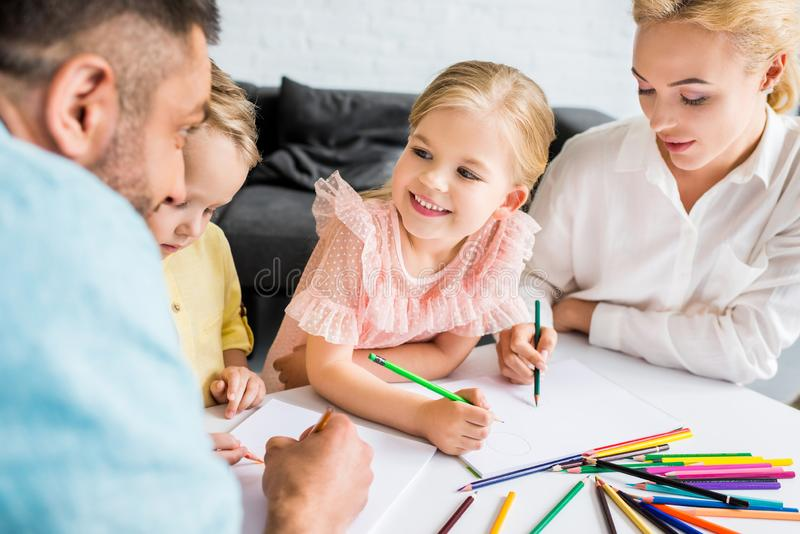 ευτυχής οικογένεια με δύο παιδιά που σύρουν με τα χρωματισμένα μολύβια στοκ εικόνα