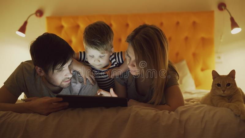 Ευτυχής οικογένεια με λίγο γιο και την αστεία γάτα που βρίσκονται στο κρεβάτι στο σπίτι και που χρησιμοποιούν τον υπολογιστή ταμπ στοκ εικόνα