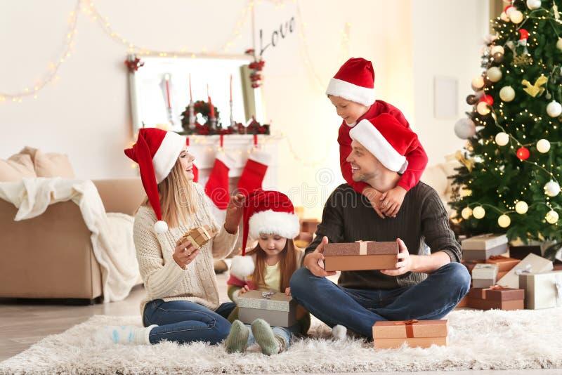 Ευτυχής οικογένεια με τα δώρα Χριστουγέννων στο σπίτι στοκ εικόνες