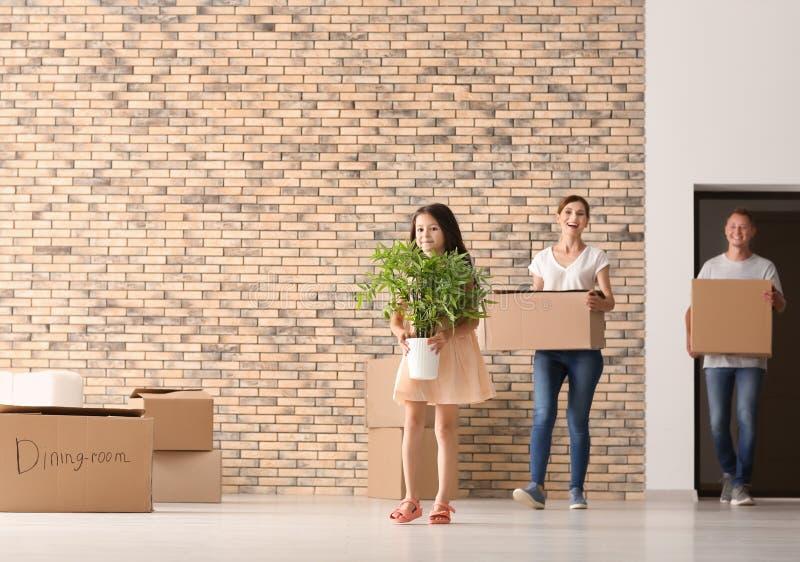 Ευτυχής οικογένεια με τα κουτιά από χαρτόνι και τις περιουσίες μετά από να κινηθεί στο καινούργιο σπίτι στο εσωτερικό στοκ εικόνες
