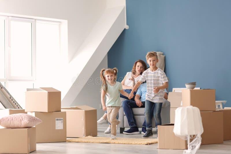 Ευτυχής οικογένεια με τα κουτιά από χαρτόνι και τις περιουσίες στο εσωτερικό Κίνηση στο καινούργιο σπίτι στοκ εικόνες με δικαίωμα ελεύθερης χρήσης