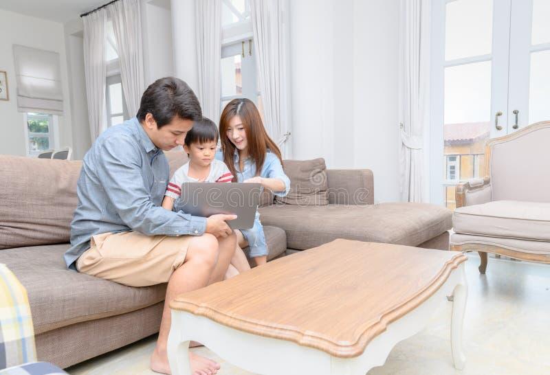 Ευτυχής οικογένεια με τα παιδάκια που απολαμβάνουν το lap-top από κοινού στοκ εικόνες