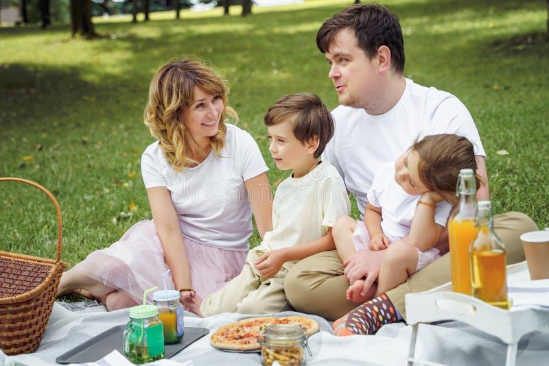 Ευτυχής οικογένεια με τα παιδιά που στηρίζονται στη χλόη κατά τη διάρκεια ενός πικ-νίκ Ευτυχία και αρμονία στη οικογενειακή ζωή στοκ εικόνες