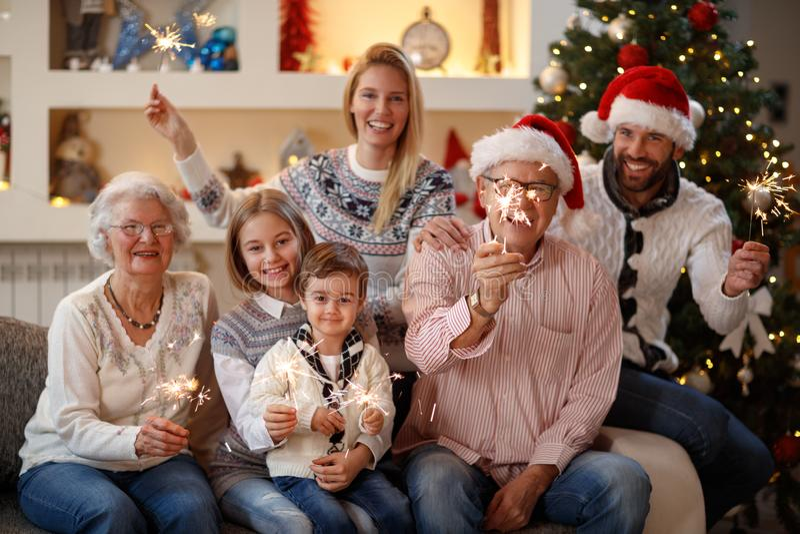 Ευτυχής οικογένεια με τα σπινθηρίσματα στη Παραμονή Χριστουγέννων στοκ εικόνες