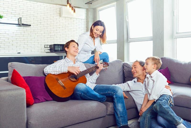 Ευτυχής οικογένεια με τα τραγούδια τραγουδιού κιθάρων στο δωμάτιο στοκ φωτογραφία με δικαίωμα ελεύθερης χρήσης