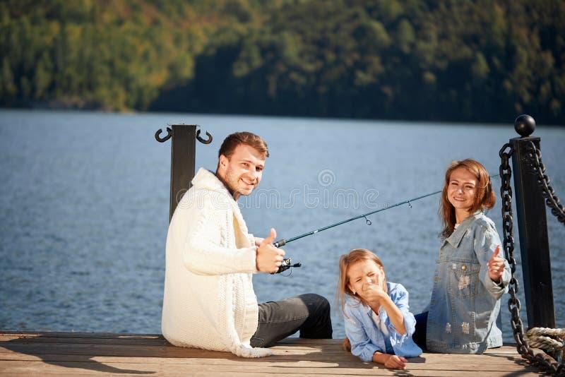 Ευτυχής οικογένεια με την αλιεία κορών στη λίμνη το φθινόπωρο στοκ φωτογραφία με δικαίωμα ελεύθερης χρήσης