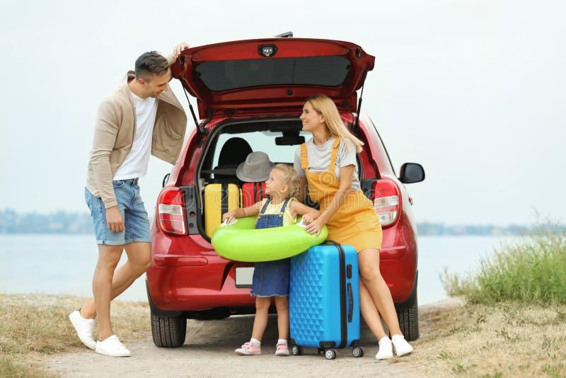 Ευτυχής οικογένεια με τις βαλίτσες και το διογκώσιμο δαχτυλίδι στοκ εικόνες
