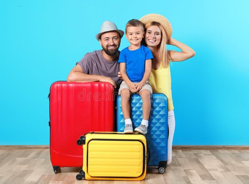 Ευτυχής οικογένεια με τις βαλίτσες κοντά στον τοίχο χρώματος στοκ εικόνες με δικαίωμα ελεύθερης χρήσης