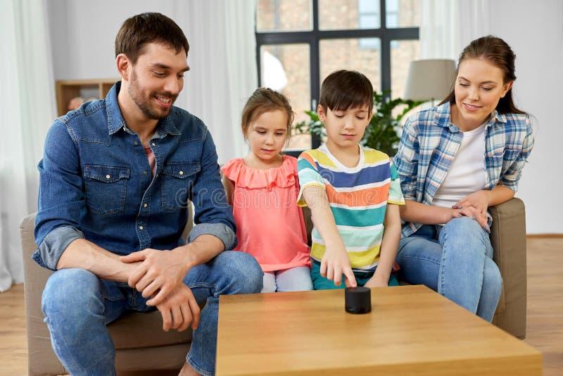 Ευτυχής οικογένεια με τον έξυπνο ομιλητή στο σπίτι στοκ εικόνα