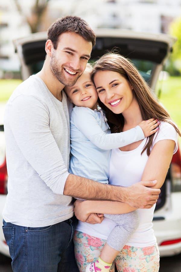 Ευτυχής οικογένεια με το αυτοκίνητο στο υπόβαθρο στοκ φωτογραφία με δικαίωμα ελεύθερης χρήσης