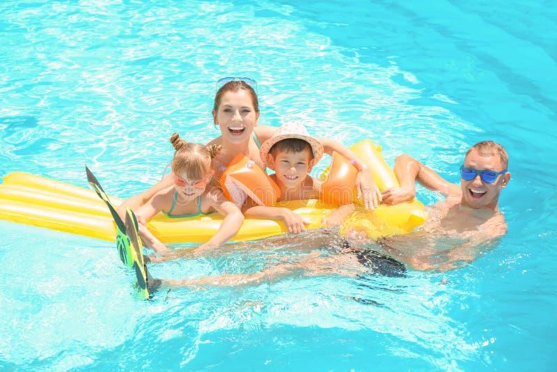 Ευτυχής οικογένεια με το διογκώσιμο στρώμα στην πισίνα στοκ φωτογραφίες