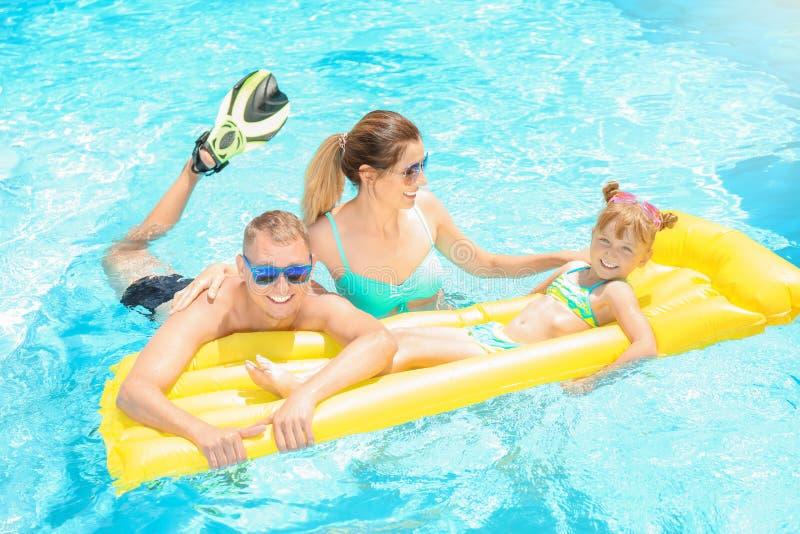 Ευτυχής οικογένεια με το διογκώσιμο στρώμα στην πισίνα στοκ εικόνα