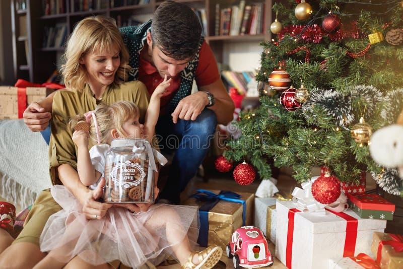 Ευτυχής οικογένεια με το μπισκότο Χριστουγέννων κοντά στο χριστουγεννιάτικο δέντρο στο σπίτι στοκ φωτογραφίες με δικαίωμα ελεύθερης χρήσης