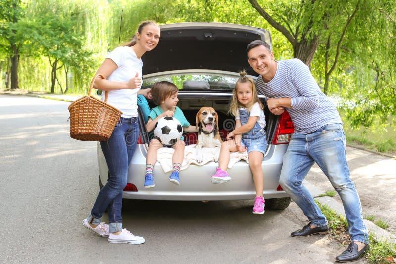 Ευτυχής οικογένεια με το σκυλί λαγωνικών κοντά στο αυτοκίνητο υπαίθρια στοκ εικόνα με δικαίωμα ελεύθερης χρήσης