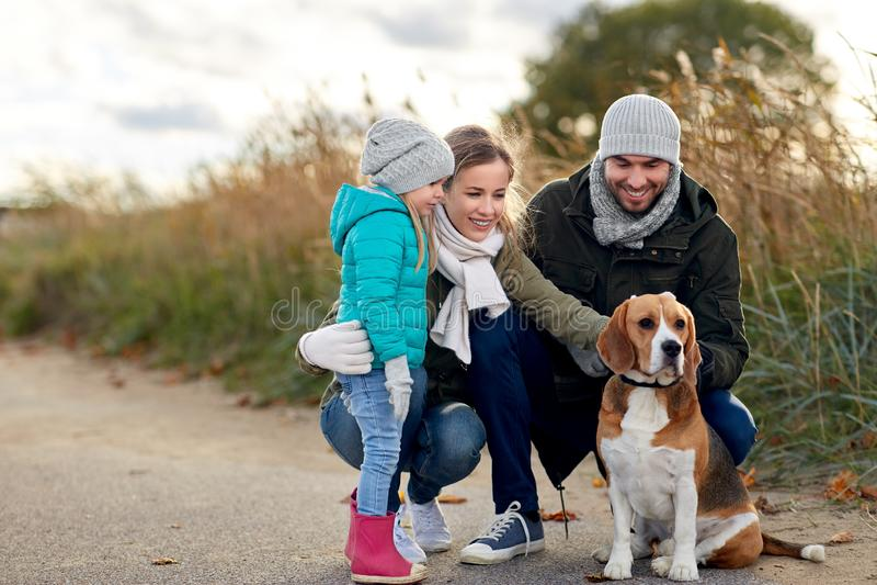 Ευτυχής οικογένεια με το σκυλί λαγωνικών υπαίθρια το φθινόπωρο στοκ εικόνες