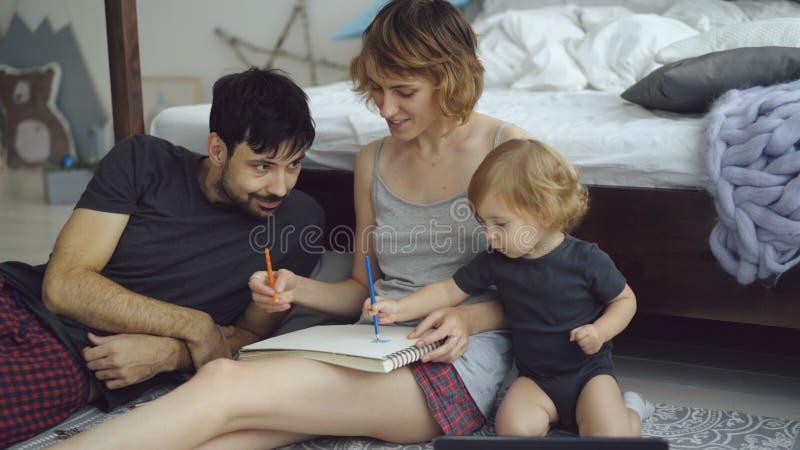 Ευτυχής οικογένεια με το χαριτωμένο λατρευτό σχέδιο κορών στο λεύκωμα με τα μολύβια που κάθεται κοντά στο κρεβάτι στο σπίτι στοκ φωτογραφίες με δικαίωμα ελεύθερης χρήσης