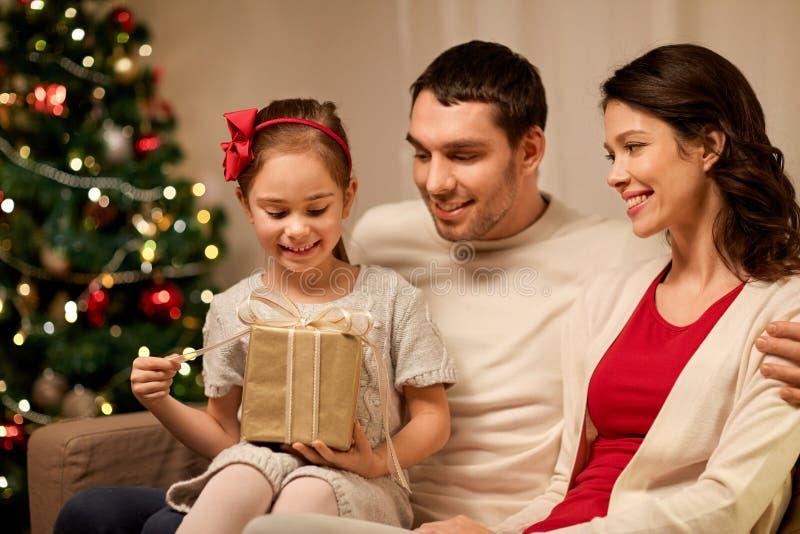 Ευτυχής οικογένεια με το χριστουγεννιάτικο δώρο στο σπίτι στοκ εικόνα