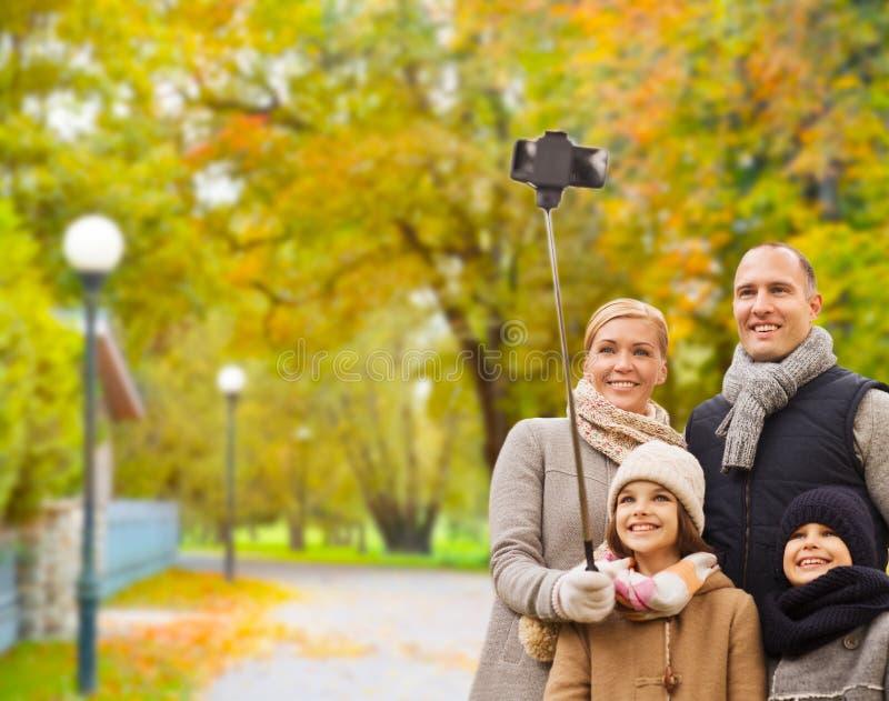 Ευτυχής οικογένεια με το smartphone και monopod στο πάρκο στοκ φωτογραφία