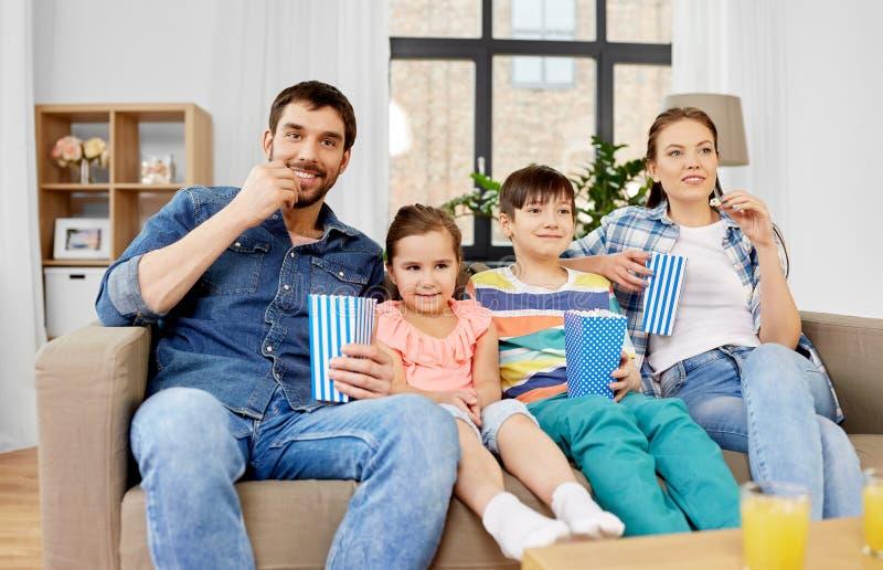 Ευτυχής οικογένεια με popcorn που προσέχει τη TV στο σπίτι στοκ εικόνες