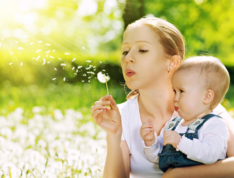 Ευτυχής οικογένεια. Μητέρα και κοριτσάκι που φυσούν σε ένα λουλούδι πικραλίδων στοκ εικόνες