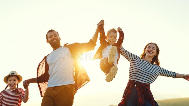 Ευτυχής οικογένεια: μητέρα, πατέρας, γιος παιδιών και κόρη στο ηλιοβασίλεμα στοκ φωτογραφία