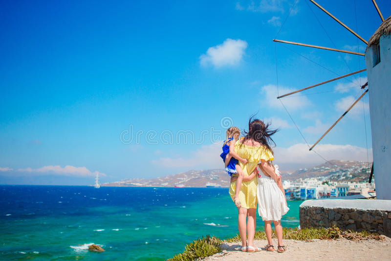 Ευτυχής οικογένεια μπροστά από τους ανεμόμυλους στη δημοφιλή περιοχή τουριστών στο νησί της Μυκόνου, Ελλάδα στοκ εικόνες με δικαίωμα ελεύθερης χρήσης