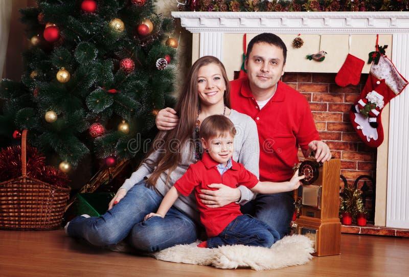 Ευτυχής οικογένεια μπροστά από το χριστουγεννιάτικο δέντρο στοκ εικόνα