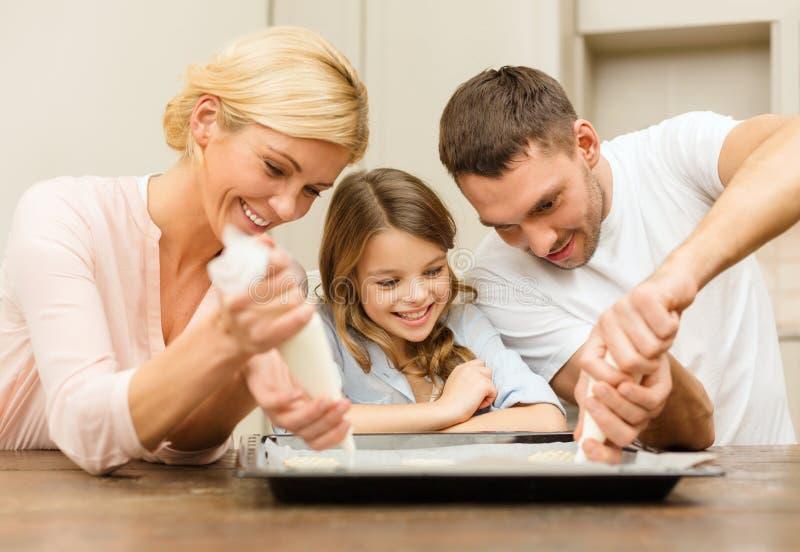 Ευτυχής οικογένεια να κατασκευάσει τα μπισκότα στο σπίτι στοκ φωτογραφίες
