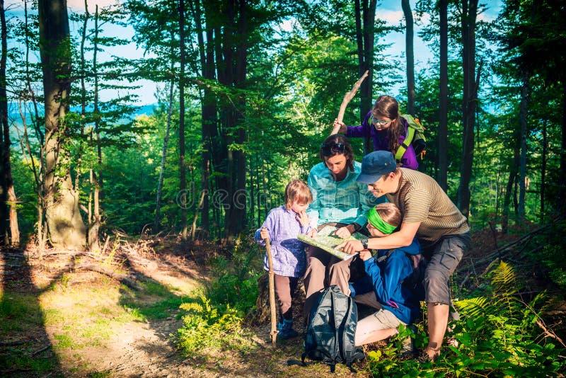Ευτυχής οικογένεια - πατέρας, μητέρα και κόρες - σε ένα ταξίδι βουνών στο δάσος που εξετάζει το χάρτη στοκ φωτογραφία