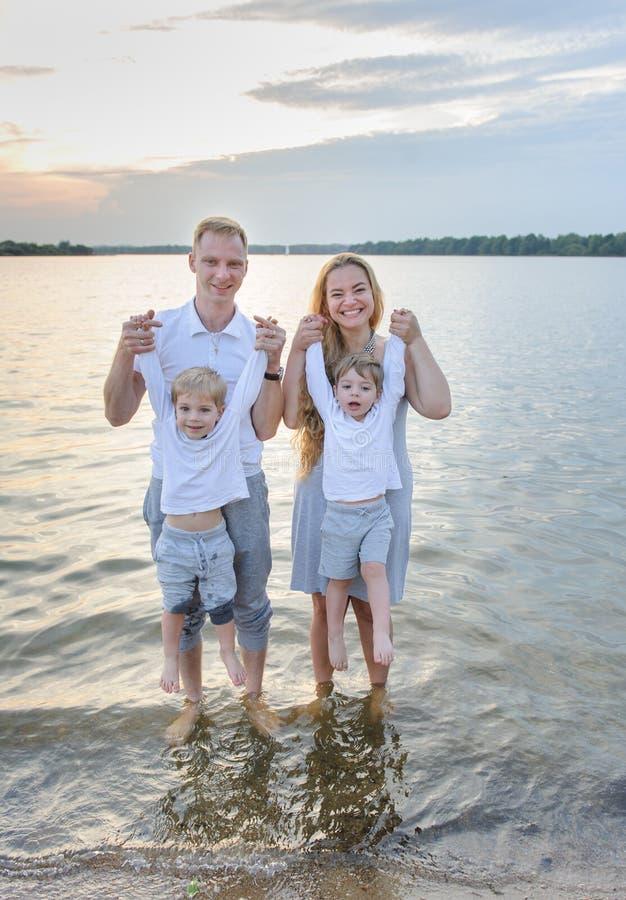 Ευτυχής οικογένεια - πατέρας, μητέρα, δύο γιοι στην παραλία με τα πόδια τους στο νερό στο ηλιοβασίλεμα στοκ φωτογραφίες με δικαίωμα ελεύθερης χρήσης