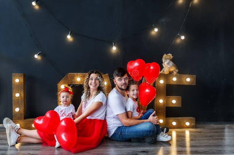 Ευτυχής οικογένεια που έχει τη διασκέδαση την ημέρα του βαλεντίνου Αγίου στο στούντιο Γονείς με τα παιδάκια με την καρδιά baloons στοκ εικόνα