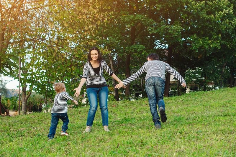 Ευτυχής οικογένεια που έχει τη διασκέδαση υπαίθρια Νέα οικογένεια που απολαμβάνει τη ζωή, μαζί στη φύση Ευτυχής οικογενειακός τρό στοκ φωτογραφία με δικαίωμα ελεύθερης χρήσης