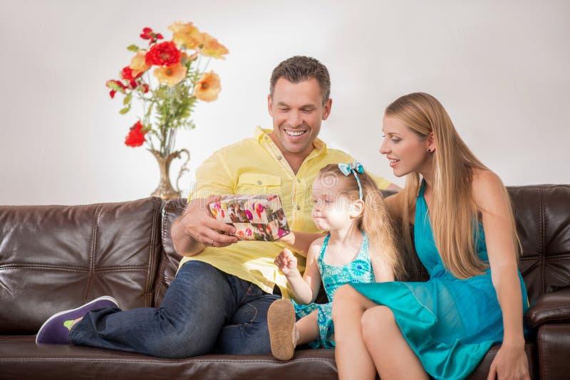 Ευτυχής οικογένεια που έχει τη διασκέδαση και που δίνει τα δώρα στοκ εικόνα