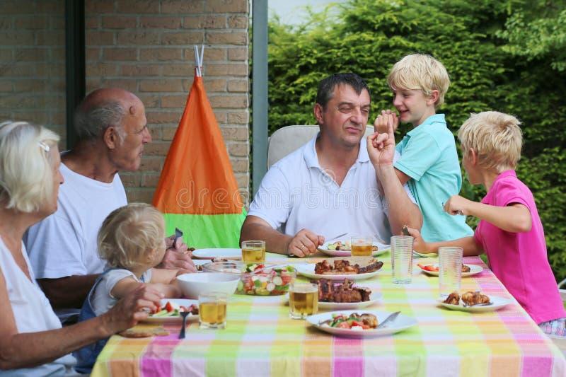 Ευτυχής οικογένεια που έχει το γεύμα από κοινού στοκ φωτογραφία