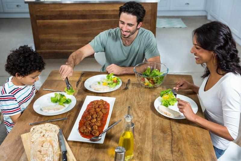 Ευτυχής οικογένεια που έχει το μεσημεριανό γεύμα από κοινού στοκ εικόνες