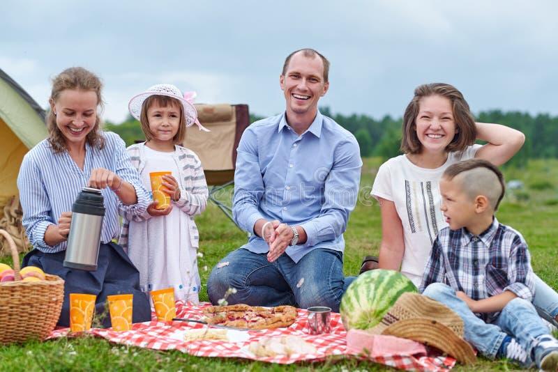 Ευτυχής οικογένεια που έχει το πικ-νίκ στο λιβάδι μια ηλιόλουστη ημέρα Οικογένεια που απολαμβάνει τις διακοπές στρατοπέδευσης στη στοκ εικόνες
