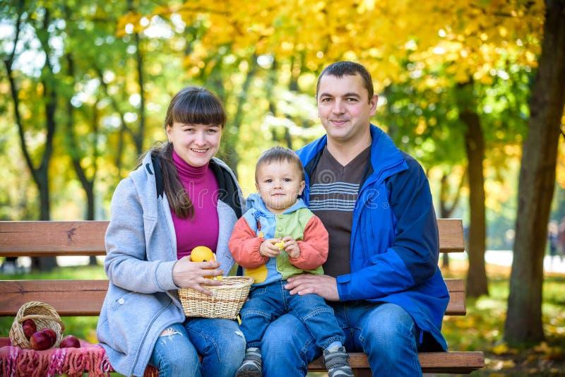 Ευτυχής οικογένεια που απολαμβάνει το πικ-νίκ φθινοπώρου Η μητέρα και ο γιος πατέρων κάθονται στον πάγκο με το καλάθι μήλων Ευτυχ στοκ εικόνα με δικαίωμα ελεύθερης χρήσης