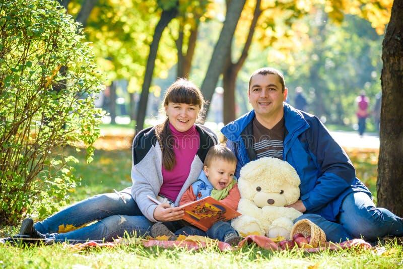Ευτυχής οικογένεια που απολαμβάνει το πικ-νίκ φθινοπώρου Η μητέρα και ο γιος πατέρων κάθονται στον τομέα με το καλάθι μήλων teddy στοκ φωτογραφία