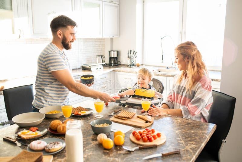 Ευτυχής οικογένεια που απολαμβάνει το πρόγευμα το πρωί στοκ εικόνες