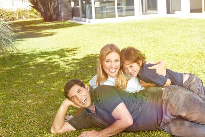Ευτυχής οικογένεια που βάζει στον κήπο ενός σπιτιού στοκ εικόνα με δικαίωμα ελεύθερης χρήσης