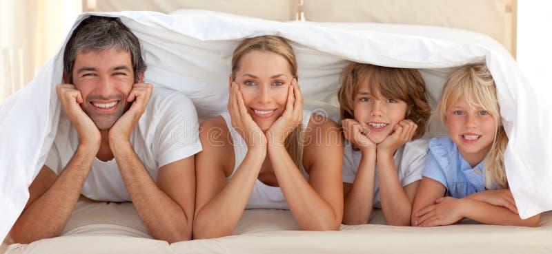 Ευτυχής οικογένεια που βρίσκεται κάτω από ένα κάλυμμα στοκ εικόνα με δικαίωμα ελεύθερης χρήσης