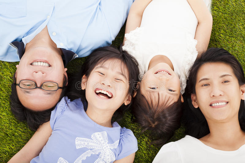 Ευτυχής οικογένεια που βρίσκεται σε ένα λιβάδι από κοινού στοκ εικόνες