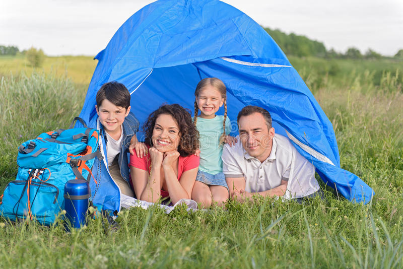 Ευτυχής οικογένεια που βρίσκεται στη σκηνή στοκ εικόνα με δικαίωμα ελεύθερης χρήσης
