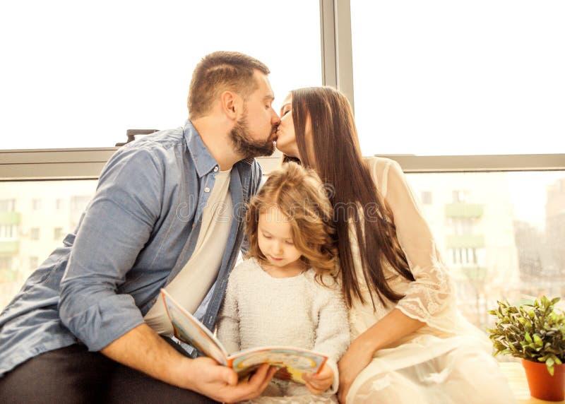 ευτυχής οικογένεια που διαβάζει ένα βιβλίο στην κόρη της στοκ φωτογραφία