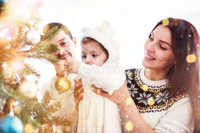 Ευτυχής οικογένεια που διακοσμεί το χριστουγεννιάτικο δέντρο από κοινού Πατέρας, μητέρα και κόρη παιδί χαριτωμένο στοκ εικόνα με δικαίωμα ελεύθερης χρήσης