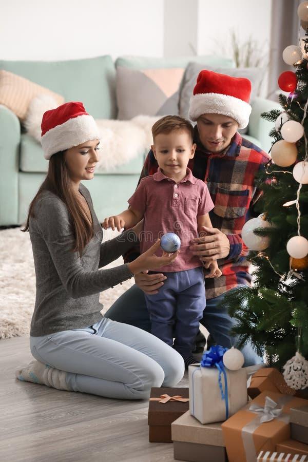 Ευτυχής οικογένεια που διακοσμεί το χριστουγεννιάτικο δέντρο στο σπίτι στοκ εικόνες με δικαίωμα ελεύθερης χρήσης